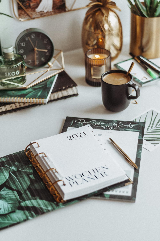Wochenplaner Greenery 2021 mit Block und Kugelschreiber auf weißem Schreibtisch mit Dekoelementen