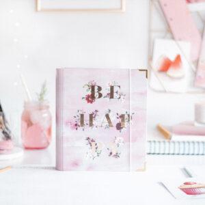 Cover Aquarell Be Happy auf einem Schreibtisch mit Infused Water und roséfarbener Deko