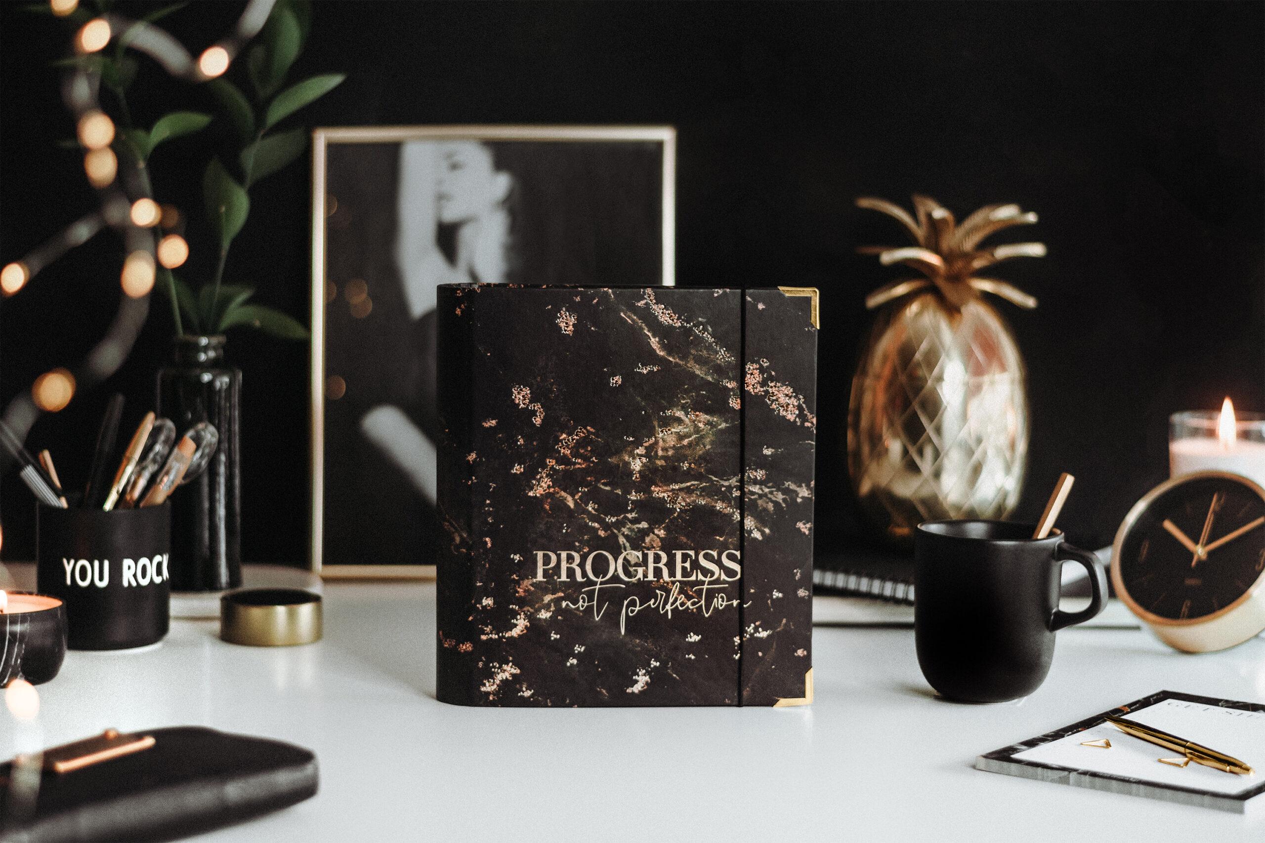 Ringbuch Black auf Schreibtisch mit schwarz-goldener Deko