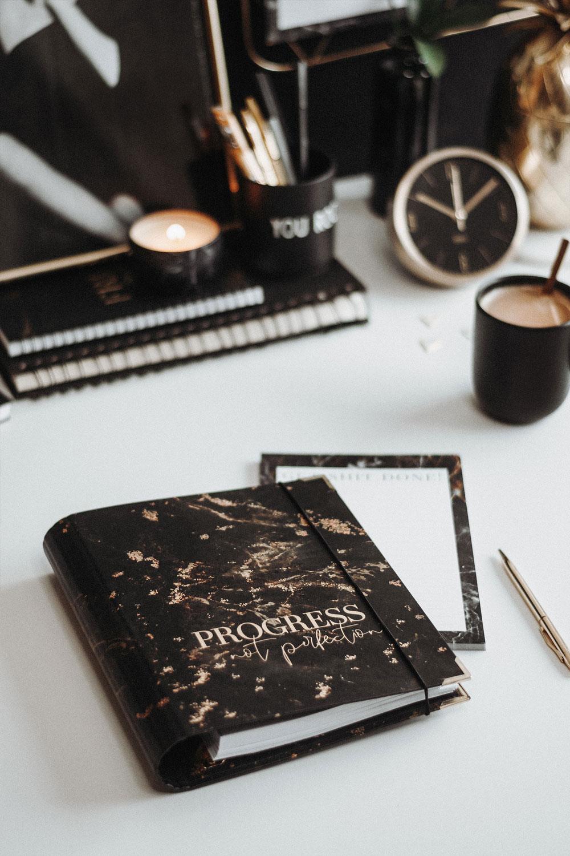 Cover Black Progress not Perfection mit Block und Kaffee auf weißem Schreibtisch