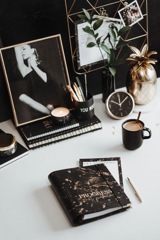 Cover Black auf einem weißen Schreibtisch mit Accessoires in schwarz und gold