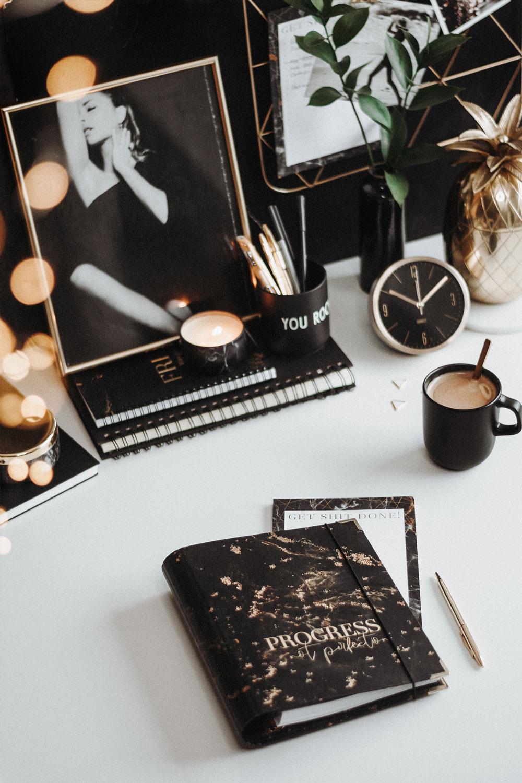 Cover Black Ringbuch mit goldenem Kugelschreiber und Kaffee auf einem Schreibtisch mit schwarzer Dekoration