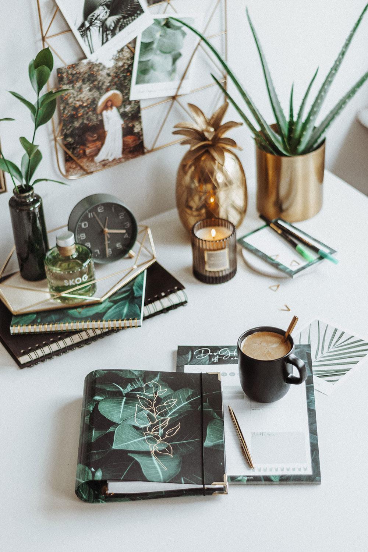 Cover Greenery mit goldenen Akzenten auf einem Schreibtisch mit grünen Pflanzen und goldenen Accessoires