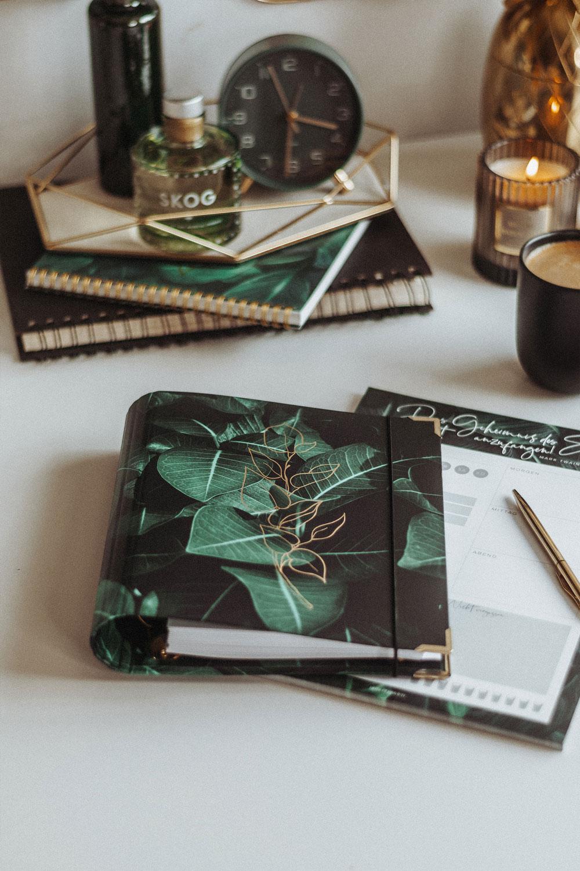 Cover Greenery Ringbuch mit goldenem Kugelschreiber auf Schreibtisch mit Dekoration