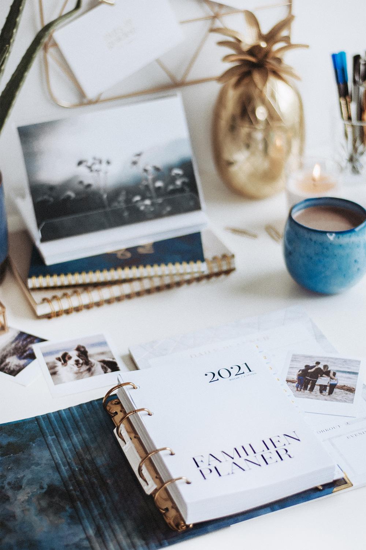 Familienplaner Midnight auf Schreibtisch mit Kaffee und Deko