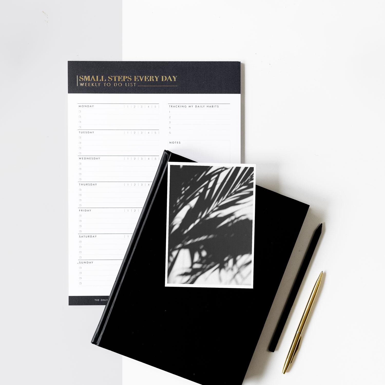 Block Small Steps und schwarzes Notizbuch mit goldenem Kugelschreiber