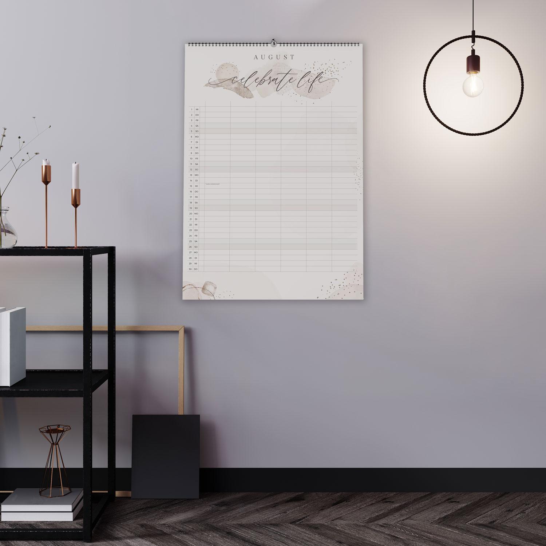 Wandkalender an lavendelfarbener Wand mit schwarzem Regal