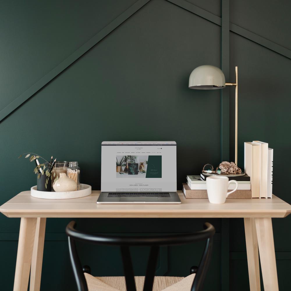 Dunkelgrüne Wand mit Holzschreibtisch und Lampe