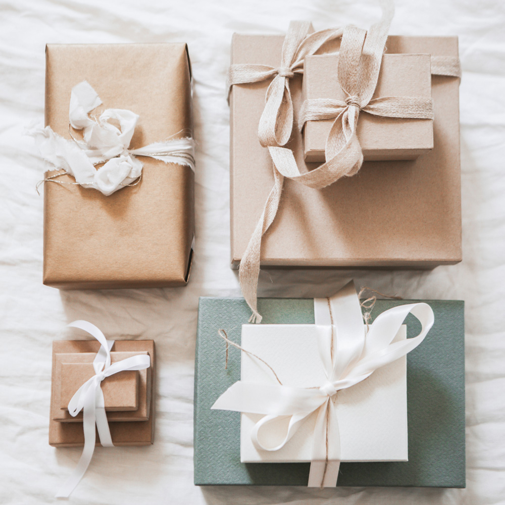 Vier Geschenke mit weißen und beigen Bändern