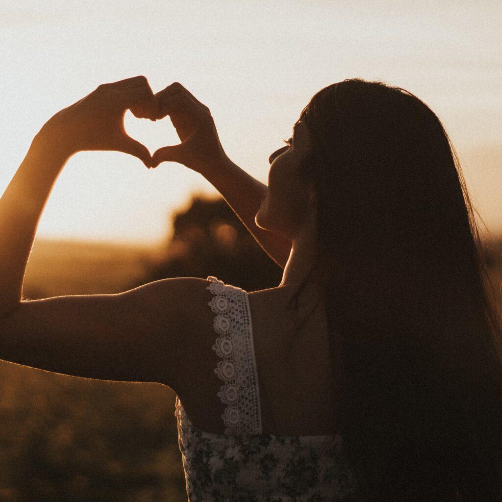Mädchen im Sonnenuntergang mit Herz